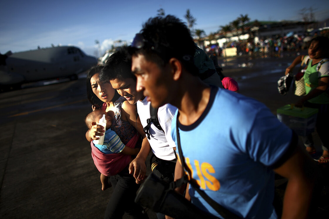 A family runs across the airport tarmac in hoping to board an emergency evacuation flight out of the devastated city.