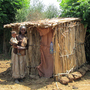 An Ethiopian woman and her child stand next to an Arborloo latrine.