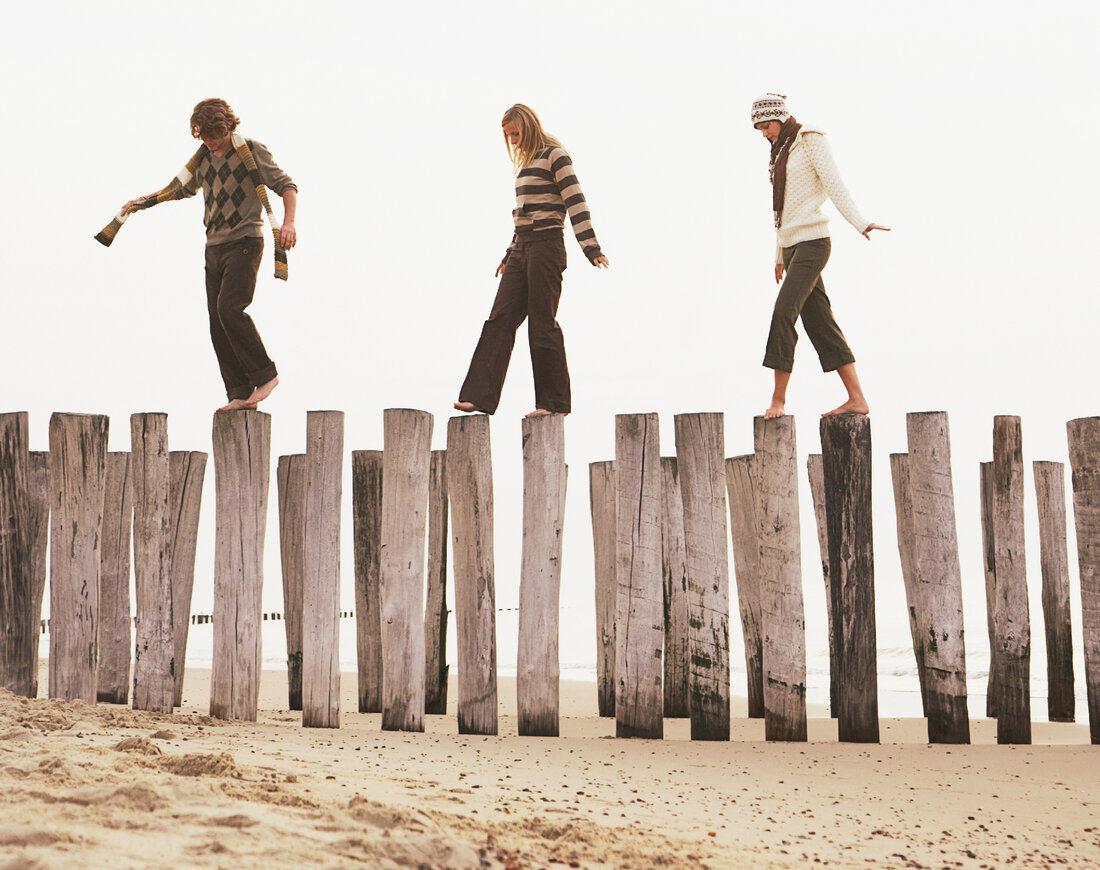 Friends balance on pilings at the beach.