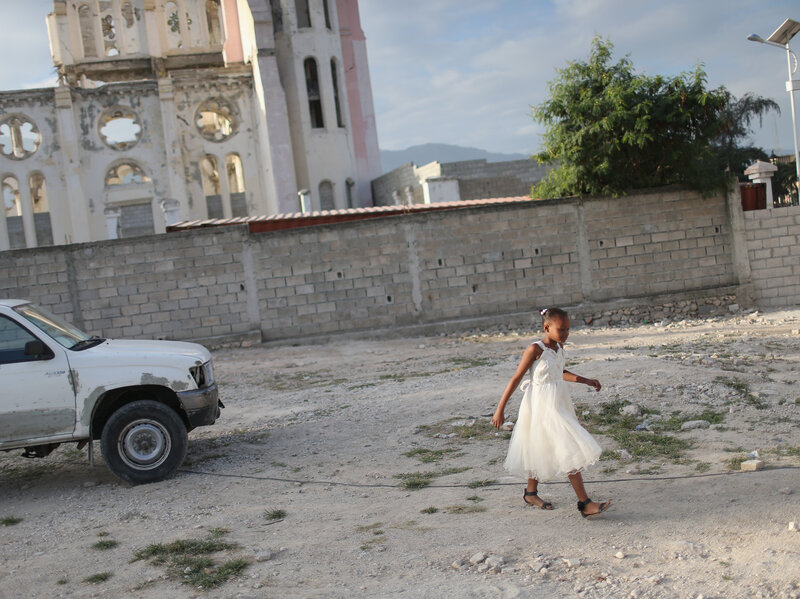 A child walks near the ruins of the National Cathedral in Port-au-Prince on Sunday. After the 2010 earthquake destroyed the cathedral, a new church was built next to the ruins.