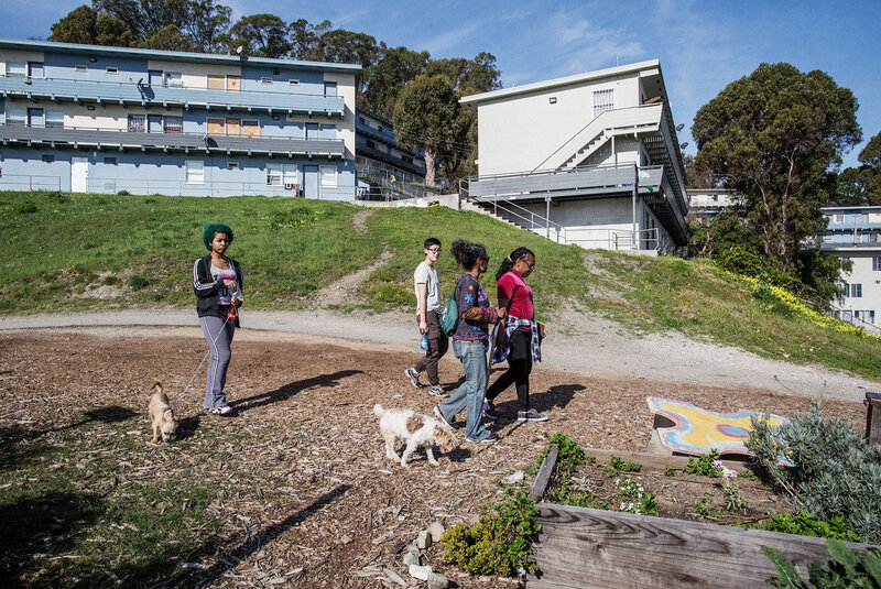 Uzuri Pease-Greene, right, leads a walk through the public housing complex in the Potrero Hill neighborhood of San Francisco where her family lives. She is working to have the old buildings replaced.
