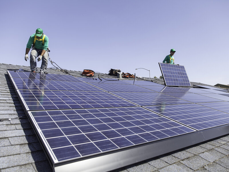 SolarCity workers installing solar panels on a rooftop.