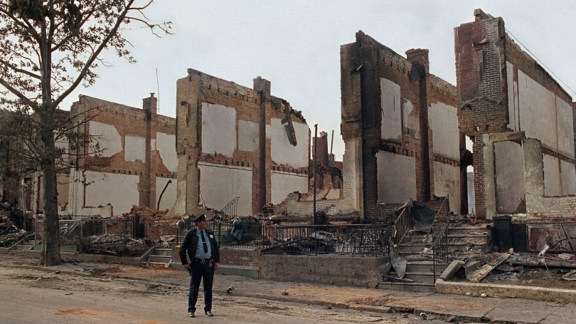 A policeman stands guard near the remains of 61 row houses