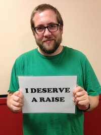"Hall holding a sign that reads ""I deserve a raise"" as part of a petition drive organized by his union."