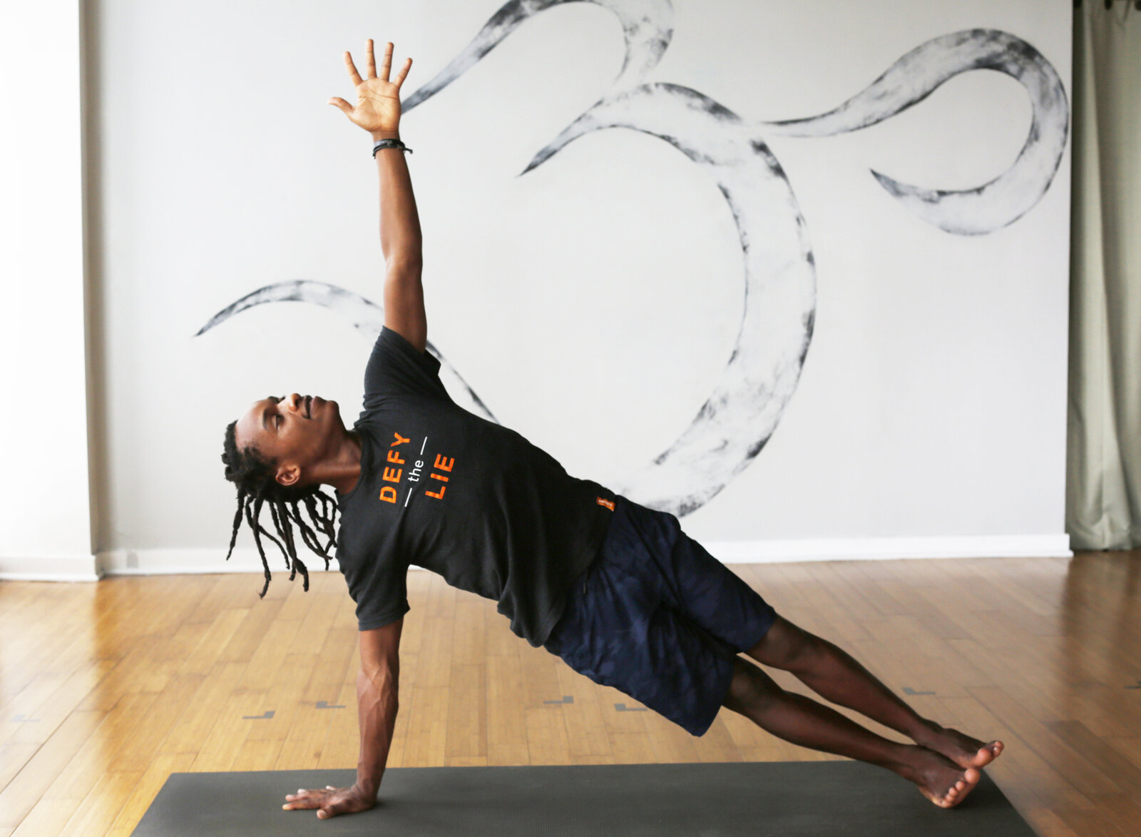 Walter Mugbe, a teacher with the Africa Yoga Project, demonstrates side plank in the Bethesda, Md., studio of Down Dog Yoga.
