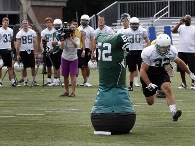 Dartmouth College Engineering graduate Quinn Connell (upper left) controls the movement of the team's Mobile Virtual Player during college football practice Wednesday.