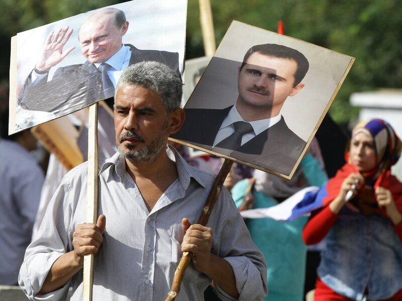 A Syrian man holding portraits of President Bashar Assad and Russian leader Vladimir Putin joins several hundred pro-government demonstrators near the Russian embassy in Damascus on Tuesday to express support for Moscow's air war in Syria. Two rockets later struck the embassy compound and sparked panic among the crowd. No one was killed.