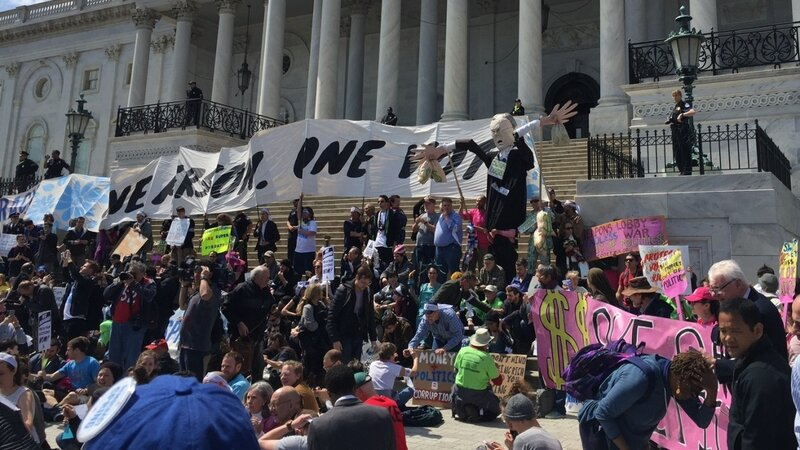 Protesters with a coalition of progressive groups sit in front of the U.S. Capitol steps Monday as part of the Democracy Spring demonstration.