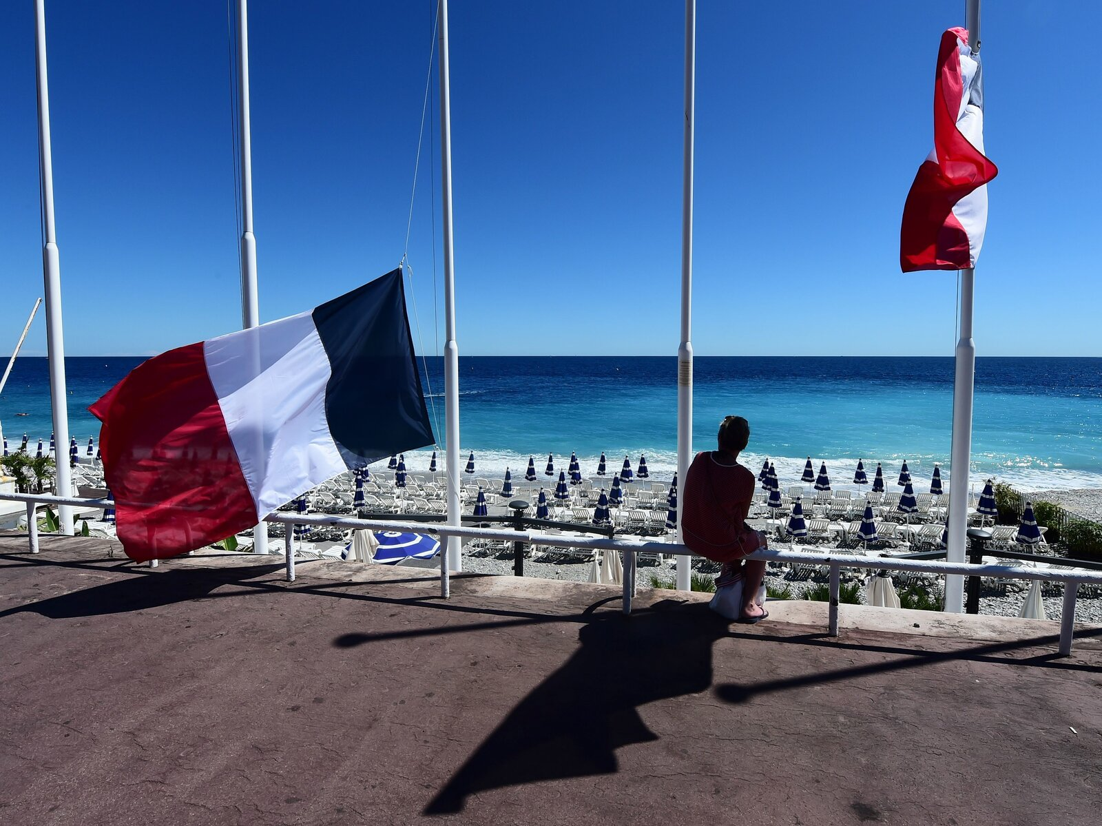 A woman sits under French flags lowered at half-mast in Nice on Friday following the deadly Bastille Day attacks.