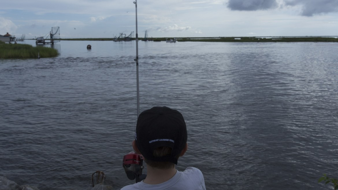 A boy fishes on a bayou near the Isle de Jean Charles, Louisiana, in August 2015. Louisiana is still losing about a football field of coastline every hour.