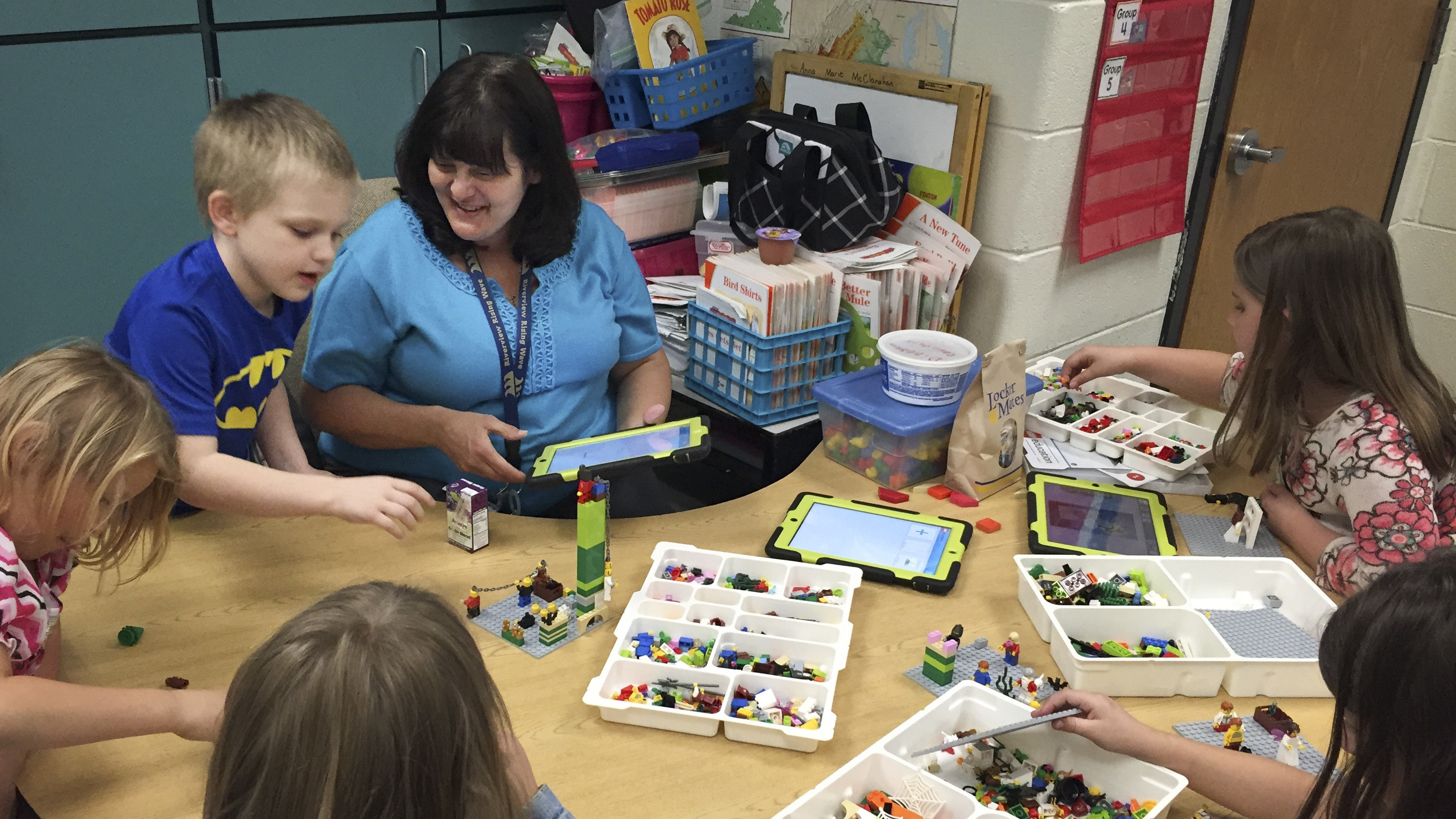 Anna Marie McClanahan (center) helps children write stories by using Legos to create scenes.