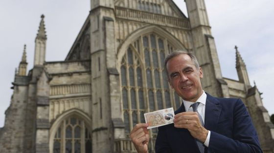 The Governor of the Bank of England, Mark Carney, poses at Winchester Cathedral in England on Tuesday, with the new 10-pound note featuring the image of Jane Austen. Two hundred years to the day since Jane Austen was laid to rest at Winchester