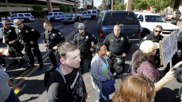 Protesters march past police officers outside the Phoenix Convention Center Tuesday.