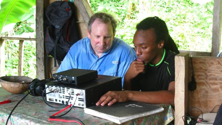 Brian Machesney (Call sign: K1LI), left, and Gordon Royner, Jr. (J73GAR), in Dominica earlier this year, discussing the operation of a ham radio set.