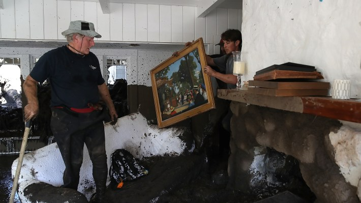 David Drenic (L) and Robert Drenic (R) look for salvageable items in a the home of a family member that was destroyed by a mudslide on Jan. 11, in Montecito, Calif.