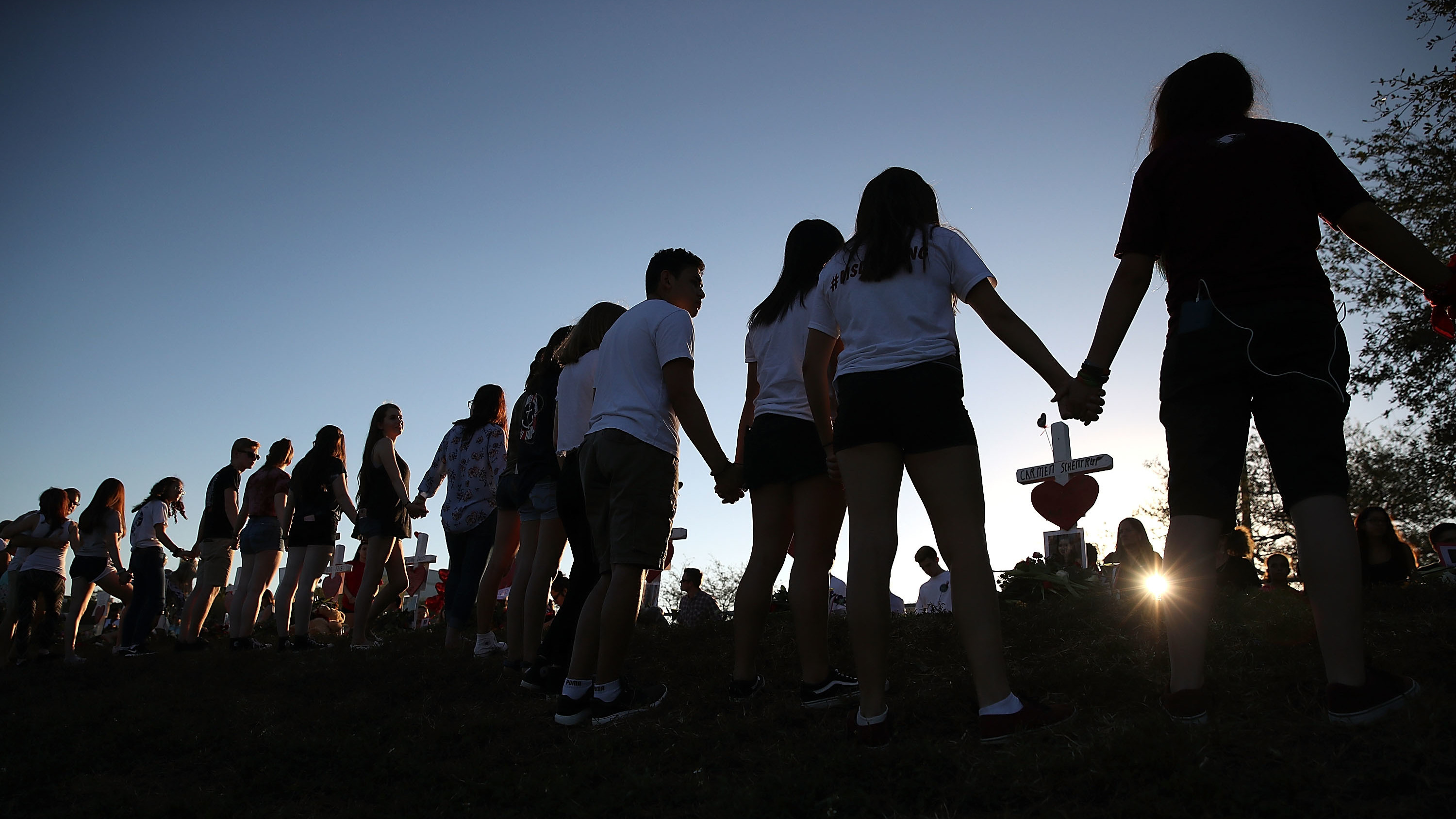 Students and family members hold hands around a makeshift memorial in front of Marjory Stoneman Douglas High School in Parkland, Fla., where 17 people were killed on Feb. 14.