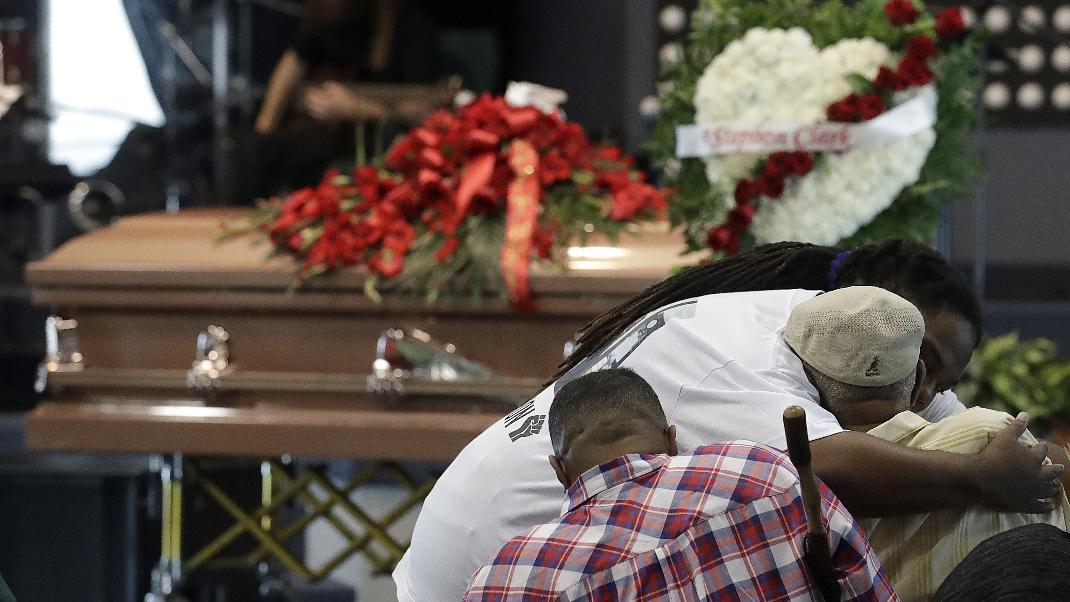 A man hugs another man during funeral services for Stephon Clark in Sacramento, Calif. Thursday.