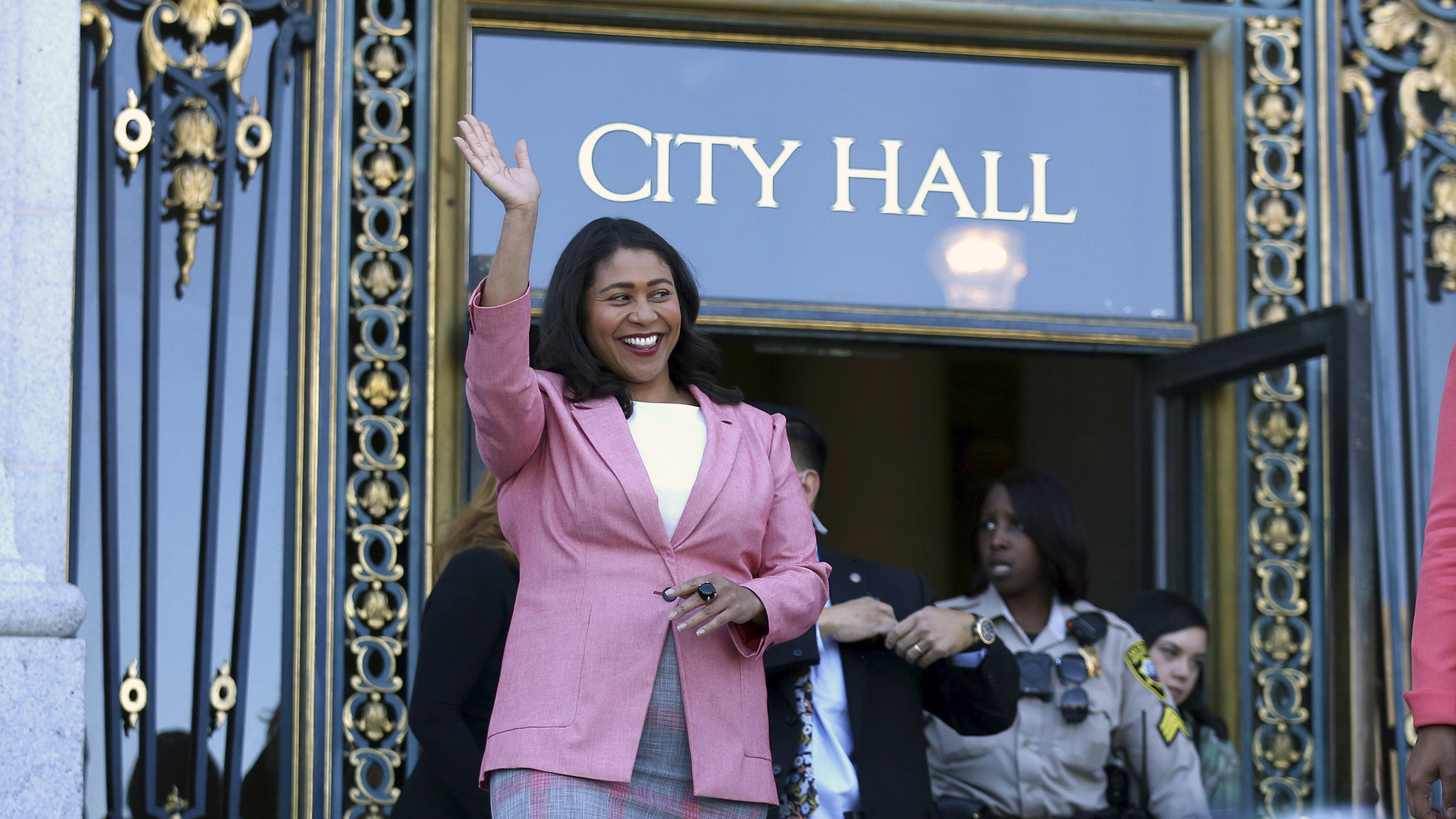 Mayor-elect London Breed waves before speaking to reporters on Wednesday outside City Hall in San Francisco.