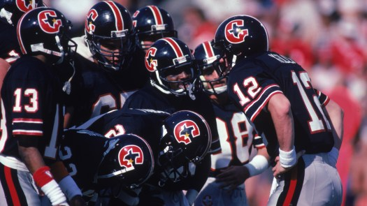 Quarterback Jim Kelly, No. 12, of the Houston Gamblers stands with his team in a huddle during a March 1985 USFL game.