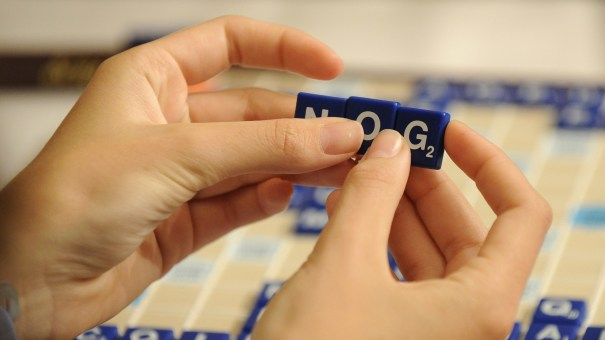 A competitor arranges letter tiles while competing in the 2008 National School Scrabble Championship, in Providence, R.I. On Monday, Merriam-Webster published a revised The Official Scrabble Players Dictionary, adding 300 new words.