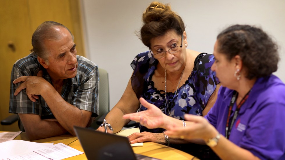 Affordable Care Act navigator Nini Hadwen (right) helped Jorge Hernandez (left) and Marta Aguirre find a plan on the health insurance exchange in Miami in 2013. Today, with fewer navigators, much of that counseling is done by phone instead of in person.