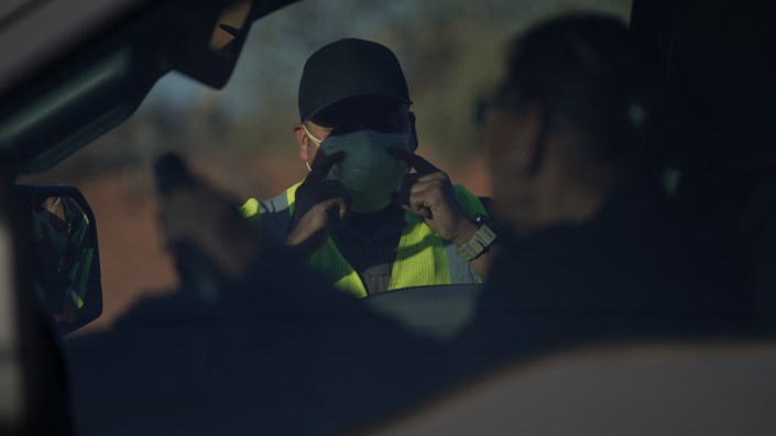 An officer with the Navajo Nation Police talks to a driver at a roadblock in Tuba City, Ariz., on the Navajo reservation on April 22, 2020.