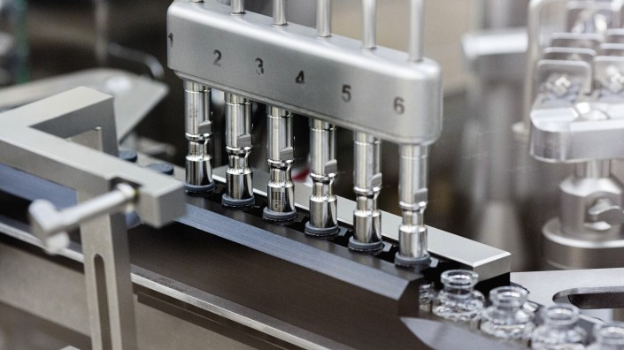 Stoppers are placed on filled vials of the experimental drug remdesivir at a Gilead Sciences factory.