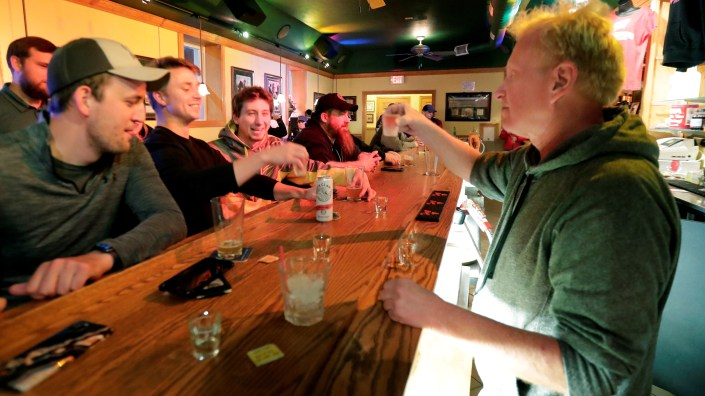 Bar owner Michael Mattson toasts with patrons as his Friends and Neighbors bar reopens Wednesday in in Appleton, Wis. Bars were able to open their doors after the Wisconsin Supreme Court struck down the state