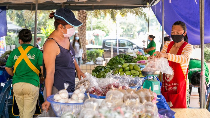 A shopper buys vegetables last month in Vientiane, Laos. The government announced that some offices and businesses will resume normal operations on Monday. The country has confirmed 19 COVID-19 cases and no deaths.