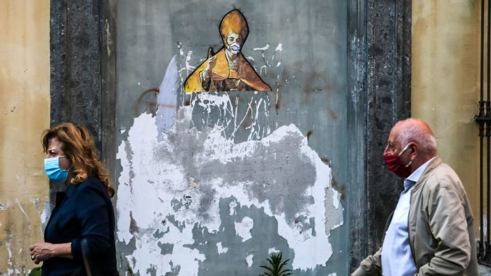 Pedestrians in face masks pass a mural in Naples depicting the city