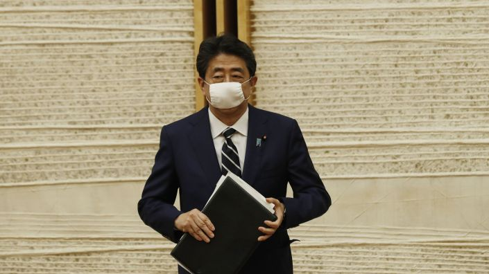 Japanese Prime Minister Shinzo Abe leaves a news conference Monday in Tokyo, after lifting the country