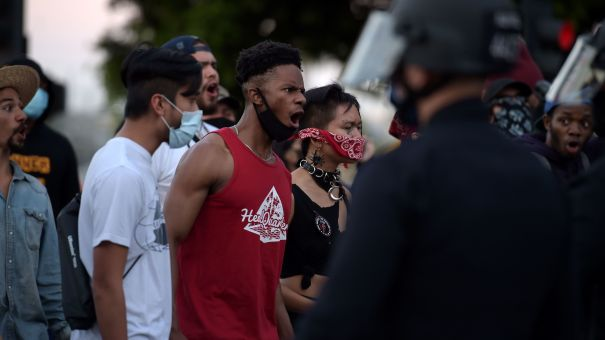 Protesters react in front of police as they gather in downtown Los Angeles on May 27, 2020 to demonstrate after George Floyd, an unarmed black man, died while being arrested by a police officer in Minneapolis who pinned him to the ground with his knee.