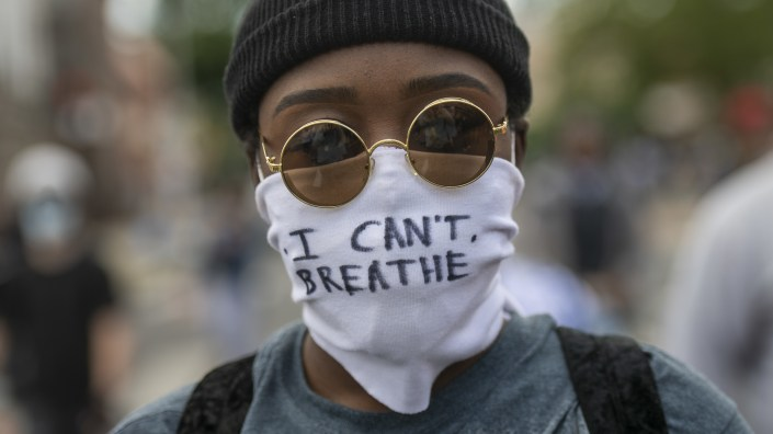 "Protests over police treatment of black people have sparked concerns over the possible spread of COVID-19. Here, a protestor marches with a cloth mask stating ""I CAN"