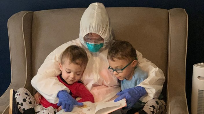 "Dr. Lauren Jenkins reads to her twin sons, Pierce and Ashton, while wearing her ""hazmat"" suit. Because lung cancer has compromised her husband"