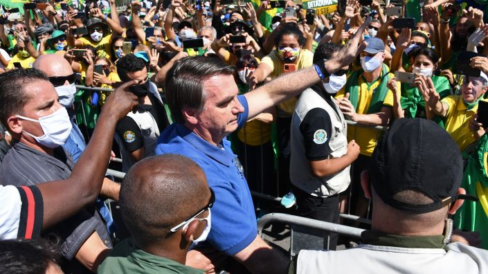 Brazilian President Jair Bolsonaro, seen greeting supporters late last month in Brasilia, has argued that the economic fallout from stay-at-home orders is worse than the virus itself.