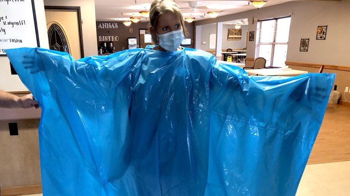 Kelly Womochil, an aide at Enterprise Estates Nursing Center in Enterprise, Kan., tries on a poncho that FEMA — the Federal Emergency Response Agency — is sending to nursing homes to protect against the coronavirus.