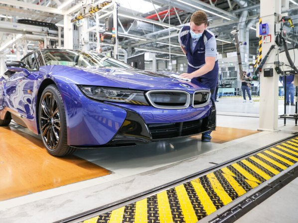 11 June 2020, Saxony, Leipzig: An employee wipes the last BMW i8 with a cloth at the end of the production line. (Photo by Jan Woitas/picture alliance via Getty Images)