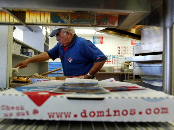Elio Blanco cuts a Domino's Pizza in Miami, Florida.