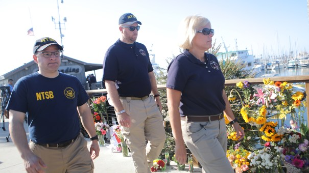 National Transportation Safety Board member Jennifer Homendy (right) walks with other NTSB officials past a makeshift memorial for victims of the Conception boat fire in September 2019 in Santa Barbara, Calif.
