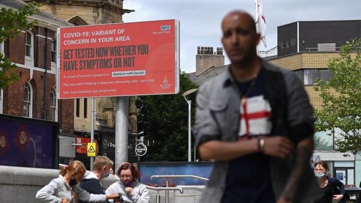 Bir işaret, insanları İngiltere'nin Blackburn kentinde bir COVID-19 varyantı için test etmeye çağırıyor.  İngiltere, ilk olarak Hindistan'da tanımlanan Delta varyantında bir artış yaşıyor.