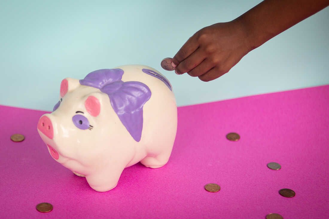 A photo of a child's hand putting a coin into a painted ceramic piggy bank. The piggy bank sits on a pink table with a blue background behind it. Coins are scattered on the table.