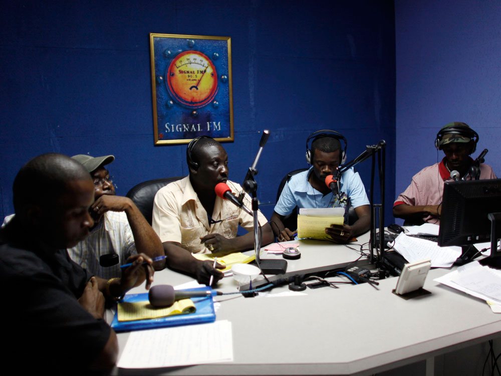 Haitian journalists broadcast from the studio of Signal FM 90.5 outside Port-au-Prince.