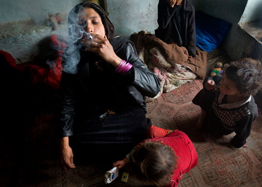 Surrounded by her children, Karima, 30, smokes heroin and opium in her one-room home in Kabul.