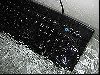 A Seal Shield computer keyboard is submerged in water in a bathtub.