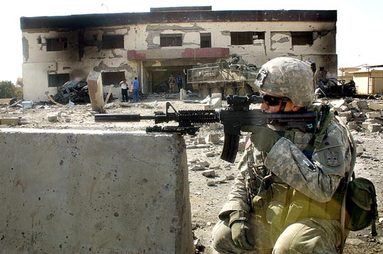 A U.S. soldier secures the area where a suicide car bomb exploded near a police station in Mosul.