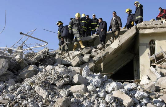 Iraqi firefighters search for wounded people amid rubble at the site of a deadly explosion in Mosul.
