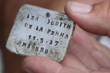 Israeli archaeologist Yoram Haimi shows aluminum plate  at the site of the former German Nazi death camp of Sobibor. Photo / AP
