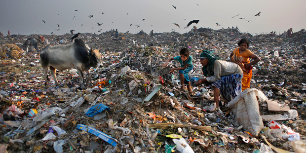 Waste pickers look for recyclable items at a landfill on the outskirts of New Delhi, India. A report by Oxfam says  not enough is being done by world leaders to tackle inequality. Photo / AP