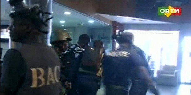 In this TV image taken from Mali TV ORTM, security forces help hostages to safety, inside the Radisson Blu Hotel. Photo / AP