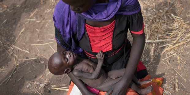 Adel Bol, 20, cradles her 10-month-old daughter Akir Mayen at a food distribution site in Malualkuel, South Sudan. Photo / AP
